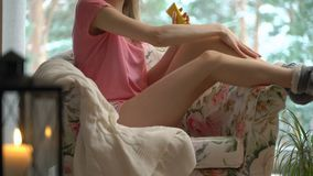 Young woman body care in cozy living room stock footage