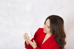 A young woman and a body cream. A young woman is observing the plastic cream box Stock Image