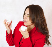 A young woman and a body cream. A young woman is observing the plastic cream box Royalty Free Stock Photos