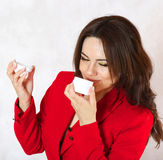 A young woman and a body cream. A young woman is observing the plastic cream box Stock Photo