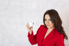 A young woman and a body cream. A young woman is observing the plastic cream box Stock Photos
