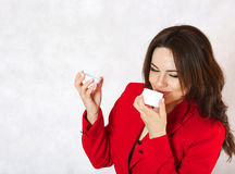A young woman and a body cream. A young woman is observing the plastic cream box Stock Images
