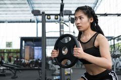 Young woman bodybuilder execute exercise in fitness center. fema Royalty Free Stock Images