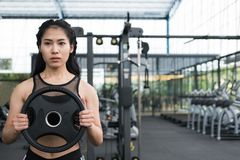 Young woman bodybuilder execute exercise in fitness center. fema Stock Image