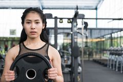 young woman bodybuilder execute exercise in fitness center. female athlete lift heavy weight barbell plate in gym. sporty girl stock photo