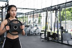 Free Young Woman Bodybuilder Execute Exercise In Fitness Center. Female Athlete Lift Heavy Weight Barbell Plate In Gym. Sporty Girl Royalty Free Stock Photo - 99300715