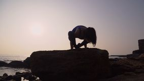 Young woman in bodysuit practicing yoga on the beach above sea at amazing sunrise. Fitness, sport, yoga and healthy. Lifestyle concept. Girl doing stand on stock video