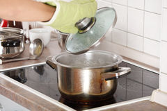 Young woman boiling something in pot Stock Image