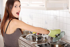 Young woman boiling something in pot Royalty Free Stock Images