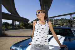 Young woman on bonnet of car beneath overpass, low angle view Stock Photography