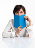 Young woman with a book. Young woman with big blue eyes holding a book, looking to the viewer on white background Royalty Free Stock Photos