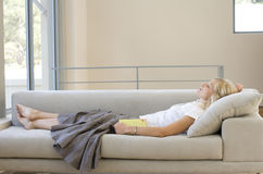 Young woman with book asleep on sofa, profile Royalty Free Stock Photography