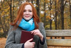 Young woman with book in autumn park, yellow leaves and trees stock images