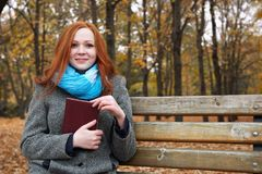 Young woman with book in autumn park, yellow leaves and trees royalty free stock photography