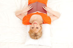 Young woman with book in bed Stock Photo