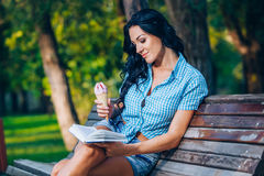 Young woman with book on the bench Royalty Free Stock Photos