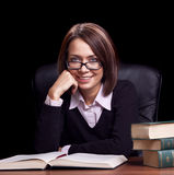 Young woman with book at the desk Stock Photo
