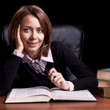 Young woman with book at the desk Stock Image