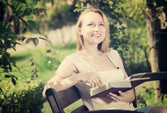 Young woman with book in garden stock photo