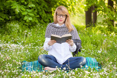 Young woman with book. Young woman with glasses reading a book in the park Stock Photos