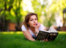 Young woman with book on green grass in city park Stock Image
