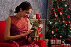 Young woman with a book in hands near the Christmas tree royalty free stock photos