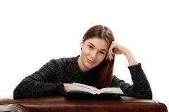 Young woman with book leaning on leather furniture Royalty Free Stock Photos