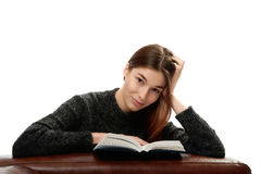 Young woman with book leaning on leather furniture Stock Photography