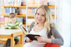 Young woman with book in library Stock Image