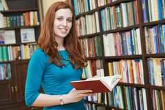 Young woman with book in library Stock Photo