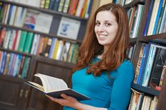 Young woman with book in library Royalty Free Stock Images