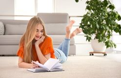 Young woman with book lying on floor. At home Royalty Free Stock Image