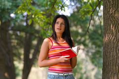 Woman in park. Young woman with book in park Royalty Free Stock Image
