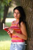 Woman in park. Young woman with book in park Royalty Free Stock Photo