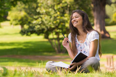 Young woman with book and pen sitting in park Stock Photography
