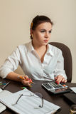 Young woman bookkeeper considers on calculator Royalty Free Stock Photography