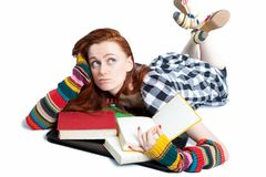 Young woman with books. Bored of daydreaming young woman lying on floor with open books; white studio background Stock Photography