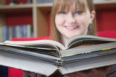 Young woman with books in library Stock Photo
