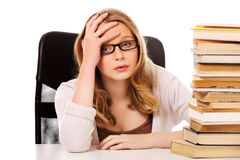 Young woman with a books pile Royalty Free Stock Photography