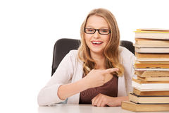 Young woman with a books pile. Happy teenage woman pointing on stack of books Stock Image