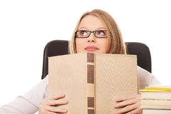 Young woman with a books pile. Pensive teenage woman with stack of books Royalty Free Stock Images
