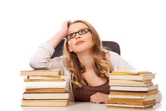 Young woman with a books pile. Pensive teenage woman with stack of books Royalty Free Stock Photos
