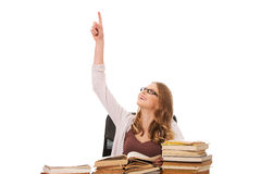 Young woman with books pile pointing up Royalty Free Stock Image