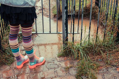 Young woman in boots standing by puddle Stock Photo