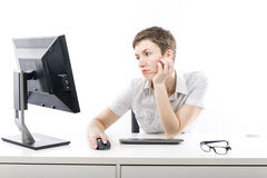 Young woman bored by computer Stock Images