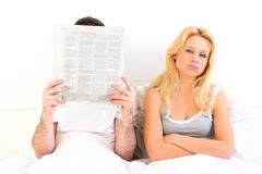 Young woman bored while her boy reading news Royalty Free Stock Image