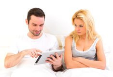 Young woman bored while her boy reading news Stock Images