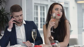 Young woman bored to date while her boyfriend having business cell on mobile phone,man busy using their smart phones at Stock Image