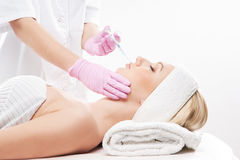 A young woman on a botox injection procedure Stock Photo