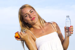 Young woman with bottle and fruit in the hand Royalty Free Stock Image